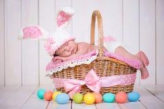 Neugeborenes Baby in einem Kaninchenkostüm hat süße Träume auf dem Weidenkorb Schöner Hintergrund Stockbild