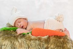 Neugeborenes Baby im Häschenkostüm schlafend auf Pelzbett stockbilder