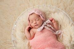 Neugeborenes Baby im Korb, der eine rosa Mütze trägt lizenzfreie stockfotos