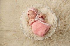 Neugeborenes Baby im Korb, der eine rosa Mütze trägt Lizenzfreies Stockfoto