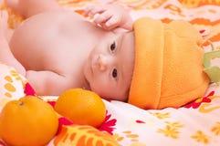 Neugeborenes Baby im orange Hut Lizenzfreie Stockbilder