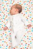 Neugeborenes Baby kleidete in weißem auf ihr zurück schlafen an Stockbilder