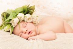 Neugeborenes Baby mit Blumen Stockfotos