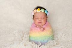 Neugeborenes Baby mit dem gefärbten Regenbogen wickeln Stockbild