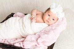 Neugeborenes Baby mit dem weißen Stirnband, das in den Korb legt Lizenzfreies Stockfoto