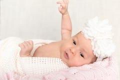 Neugeborenes Baby mit dem weißen Stirnband, das in den Korb legt Lizenzfreies Stockbild