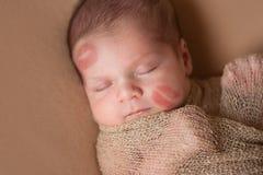 Neugeborenes Baby mit Lippenstift-Küssen auf Gesicht Lizenzfreie Stockfotos