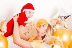 Neugeborenes Baby mit Mutter auf dem Hintergrund von Weihnachtsbällen Stockfotografie