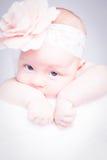 Neugeborenes Baby mit Stirnband auf dem Kopf, der auf Decke liegt stockfoto