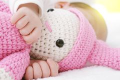 Neugeborenes Baby schläft mit einem rosa Spielzeugbaby und Handumarmungen stockfotos