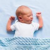 Neugeborenes Baby unter einer blauen Decke Lizenzfreies Stockbild