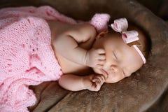 Neugeborenes Babyschlafen nett, bedeckt mit dem weichen rosa Schal, ordentlich gefaltet unter einem Stift mit einem kleinen Kopf  stockfotografie