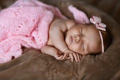Neugeborenes Babyschlafen nett, bedeckt mit dem weichen rosa Schal, ordentlich gefaltet unter einem Stift mit einem kleinen Kopf  stockbilder