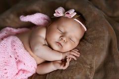 Neugeborenes Babyschlafen nett, bedeckt mit dem weichen rosa Schal, ordentlich gefaltet unter einem Stift mit einem kleinen Kopf  stockfoto