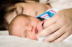 Neugeborenes Kinderkind, das nahe bei Mutter nach Lieferung stillsteht Stockfoto