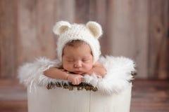 Neugeborenes Mädchen, das einen weißer Bärn-Hut trägt Stockfotografie