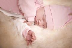 Neugeborenes Mädchen in einem rosa Kleid schlafend auf Schaffell stockbild
