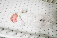 Neugeborenes Mädchen gekleidet als Erbse, die im Bett in einem weißen Stoffstern liegt Stockbilder