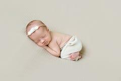 Neugeborenes Mädchen im Hairband schlafend auf ihrer Seite Lizenzfreie Stockfotos