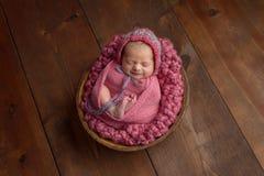 Neugeborenes Mädchen, das in der hölzernen Schüssel schläft Lizenzfreie Stockbilder