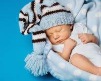 Neugeborenes Porträt des Babys, Kind, das im blauen Hut schläft Stockfotos