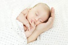 Neugeborenes Schätzchen, das auf Muttergesellschafthand schläft. Stockbild