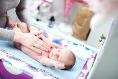 Neugeborenes Schätzchen, das im Bett gestreichelt von der Mutter liegt Lizenzfreies Stockfoto