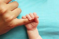 Neugeborenes Schätzchen, das Mutterfinger kuppelt Lizenzfreie Stockfotos