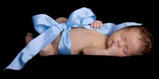 Neugeborenes Schätzchen eingewickelt, oben beim Farbband-und Bogen-Schlafen Stockbild