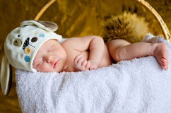 Neugeborenes Schlafen mit einem flaumigen Endstück im Hut lizenzfreie stockfotografie