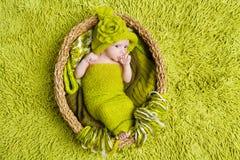 Neugeborenes Schätzchen im woolen grünen Hut innerhalb des Korbes Lizenzfreie Stockfotografie