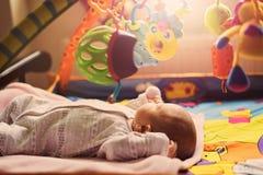Neugeborenes Spielen des netten kleinen Säuglingsbabys mit Spielwaren auf buntem MA Lizenzfreie Stockbilder
