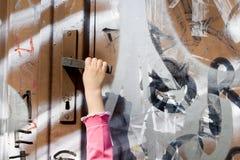 Neugier des kleinen Mädchens - Hand und Tür Stockfotografie