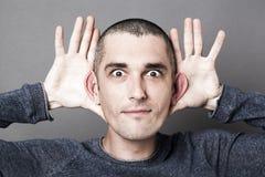Neugier und Anhörung für den Mann, der Größe von Ohren hervorhebt Stockbilder