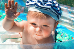 Neugierig, glücklich, zehn Monate alte Baby, die auf blauem Pool aufwerfen Lizenzfreies Stockbild