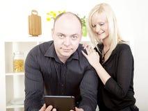 Neugierige Frau, die ihre Ehemanntablette liest Lizenzfreie Stockbilder