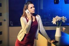 Neugierige Brunettefrau, die am Telefon spricht stockfotografie
