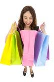 Neugierige Geschenkfrau, die Einkaufstasche untersucht Lizenzfreie Stockfotografie