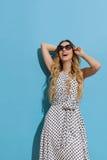 Neugierige junge Frau in der Sonnenbrille schaut oben und Lächeln Lizenzfreie Stockfotografie