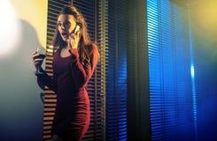 Neugierige junge Frau, die am Handy spricht stockfotografie