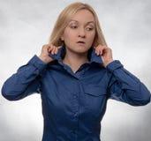 Neugierige junge Frau im zufälligen blauen Hemd mit den Händen im Haar lizenzfreie stockfotos