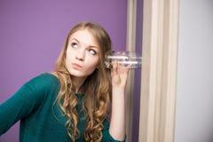 Neugierige junge Frau mit Glas Stockbild