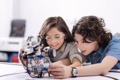 Neugierige Kinder, die in der Schule mit Roboter spielen Stockfotografie