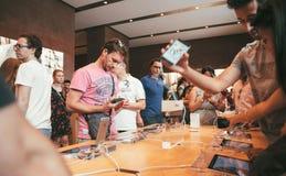 neugierige Kunden innerhalb Apple Stores das lates iPhone bewundernd Lizenzfreie Stockbilder