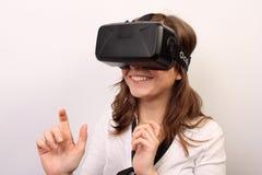 Neugierige, lächelnde Frau in einem weißen Hemd, tragender Kopfhörer virtuellen Realität 3D der Oculus-Riss-VR, etwas erforschend