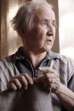 Neugierige ältere Dame Knitting Stockfoto