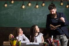Neugierige nette Kinderhörender Lehrer mit Aufmerksamkeit Lehrer- und Mädchenschüler im Klassenzimmer, Tafel an stockfoto