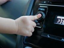 Neugieriger asiatischer Baby ` s Finger, der einen Knopf eines Autoaudiosystems drückt stockbilder