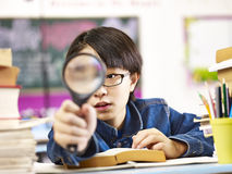 Neugieriger asiatischer Schüler, der ein Vergrößerungsglas vor einem Auge hält lizenzfreies stockbild