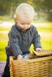 Neugieriger blonder Baby-Öffnungs-Picknick-Korb draußen am Park Lizenzfreies Stockfoto